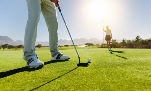 Golfer beim einlochen und Frau hält Stange